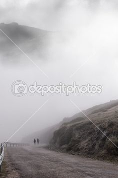 Women walking through the thick foggy mountain road one cold autumn day