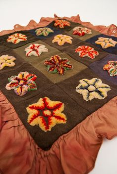 Amish or Mennonite Stumpwork from Lancaster Co., PA    Wonderful raised six pointed stars and delicate red cotton trim (please note the delicate red border does have some small holes) decorate this early folk-art textile from Pennsylvania attributed to the Amish. The bright rainbow yarnin this example plays well against the somber wool squares.