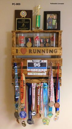 This is item #: PC-003 and it is made from a spruce wood pallet that I stained Golden Oak. It uses brass square bend hooks and rebar to hang your medals, and it has a low profile clamp for your race bibs. Along with a top shelf for trophies, pictures, etc., it also has an additional shelf to display even more race bling such as those hard earned pint glasses. <SOLD>