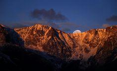 Full moon setting behind Pikes Peak.