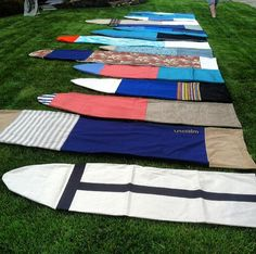 a bunch of short board and longboard surfboard bags laid out on the lawn