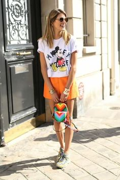 Helena Bordon's Best Street Style Outfits - Mickey Mouse graphic t-shirt, high-waisted a-line orange shorts, + a rainbow chevron print mini backpack