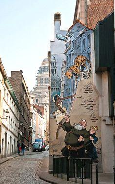 """-rue des Capucins 13-La série de fresques qui décorent les façades du centre de Bruxelles se clôture avec la série """"Odilon Verjus"""", imaginée par Yann et Verron. Cette trentième peinture murale fut inaugurée le 16 juin 2004. Elle représente, offrant leur aide à la légendaire Joséphine Baker, le robuste père Odilon Verjus et son jeune acolyte, le père Laurent."""