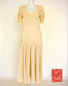 Romantic Boho Lace Italian Vintage Dress in pale cream. Shoulder and back is beautiful intricate detailed lace V neckline and embroidered in pearls. Removable padded shoulders. The bodice is a stretchy material which skims the waist and hips ending in a V shape with an embroidered finish. The loose flowing skirt finishes this elegant and feminine dress.