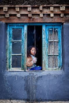 Girl by the window in Kibber village, Spiti Valley, Himachal Pradesh, India