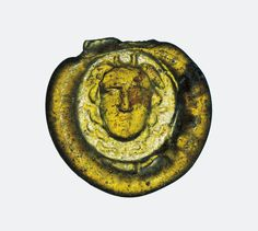 Transparent yellowish-amber glass; stamped. Roughly circular disc with suspension loop (missing); obverse: circular stamp bearing winged head of Medusa in relief. Reverse, plain.