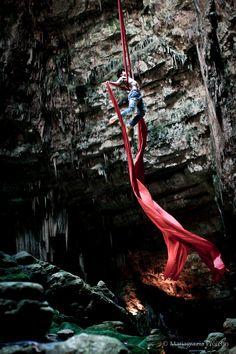Nico Gattullo performs aerial silks act Ulisse in jeans in Castellana Caves, Apulia