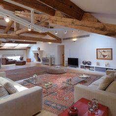 Un grande salotto con soffitto inclinato, #travi in legno a vista e pavimento in #parquet