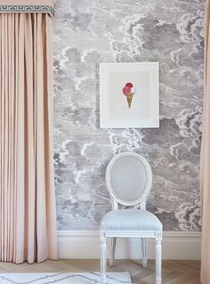 Sweetness and sophistication feminine bathroom: soft pink drapes framed by Greek key pattern, dreamy cloud-print soft grey wallpaper from Cole & Son, antique chair in white