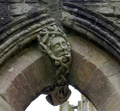 Green Man Fountains Abbey. The Green Man is thought to be a symbol of another religion apart from Christianity (possibly Paganism), and can be found in many churches, abbeys and cathedrals across the UK. On the inside of the window, is the statue of an angel holding a scroll. the scroll has the date 1883 etched into it. This is perhaps the date at which the statues were fitted to the window to prevent the window from cracking any further.