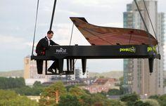 Un cascadeur fait semblant de jouer du piano en l'air alors que son instrument de carton est soulevé par un ballon à air chaud au-dessus de Vilnius en Lituanie le 10 août 2012 durant le festival d'été Piano.lt. Vilnius est l'une des rares capitales européennes permettant aux montgolfières de survoler la ville. AFP PHOTO / PETRAS MALUKAS