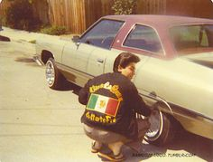 bay area lowrider wearing a black derby jacket with car club/colors....1980's or?