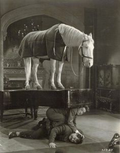 Stan Laurel  Oliver Hardy in 'Wrong Again' (1929, director Leo McCarey) Original production still caption: Laurel & Hardy discover it was famed painting, Blue Boy, they were supposed to deliver and put on the piano. They brought Blue Boy, the horse, who appears to be on top of the situation.