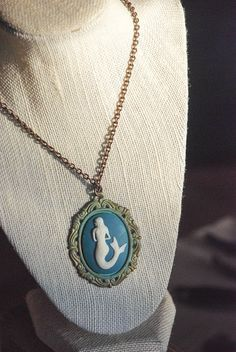 "Maiden of the Deep $21.00 This deep sea siren is set on a patina brass setting and descends from a 17"" antiqued brass chain and adorned with a fish clasp for an added nautical touch.  Lead and nickel free."