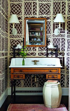Tom Scheerer.In the powder room of the Hobe Sound home, Scheerer converted a French faux-bamboo dressing table found on 1stdibs into a washstand whose fretwork is enhanced by the brown-and-cream Lyford Trellis wallpaper by Quadrille.