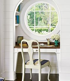 The space beneath a round, porthole-inspired window is closed in to create an office nook. Shelves in the niche around the window are a hiding spot for books, and the desk's wood top further enhances the subtle nautical theme.