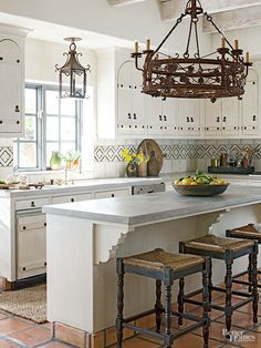 For those with smaller homes or budgets, let this modest-size kitchen inspire. It might not command the same attention as sprawling Tuscan spaces, but it still catches the eye with its elegant arched cabinets, intriguing iron knobs, pretty patterned backsplash, and oversize chandelier. Even simple Tuscan style can be stunning./