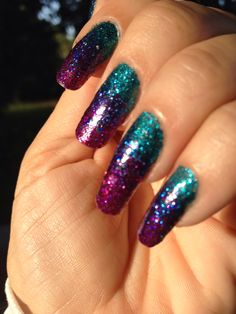 Ombré glitter manicure in teal, purple, and magenta.