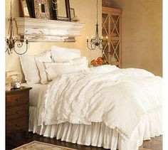I love the look of this room--especially the ruffled comforter and the mix of white linen with dark wood