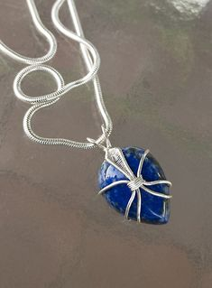 "Introducing the ""Phantasm"" PendantThis beautiful pear cut lapis lazuli pendant is wrapped in silver-plated wire to create a whimsical, one-of-a-kind pendant."