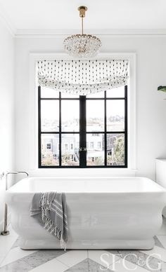 A Hydro Systems tub is tucked into the master bathroom under a vintage chandelier from 1stdibs; Jim Thompson window shade fabric is from Shears & Window.