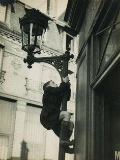 poboh: Jeune garçon grimpant sur un réverbère, Paris / Young boy climbing on a lamppost, Paris, ca 1935, André Kertész.