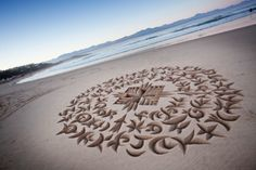 South African calligrapher Andrew van der Merwe has developed various wedge- and scoop-shaped tools to allow him to carve letters out of beach sand.