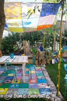 """Bunter Sitzplatz im Garten. Der Boden aus quadratischen Betonplatten wurde mit Hilfe von Schablonen bunt mit Mustern bemalt. Das Sonnensegel ist selbst genäht. Tolle DIY- Idee aus dem Buch """"Mein bunter Garten"""" von Bine Brändle"""