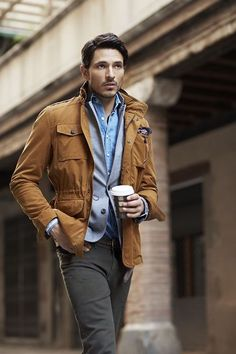 Shop this look for $269:  http://lookastic.com/men/looks/military-jacket-and-blazer-and-longsleeve-shirt-and-chinos-and-belt/443  — Tobacco Military Jacket  — Grey Blazer  — Blue Longsleeve Shirt  — Charcoal Chinos  — Brown Leather Belt