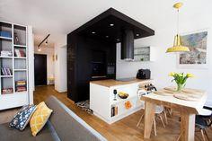 Czarne meble, ściana pomalowana tablicową farbą i podwieszany sufit z wpuszczanymi oprawami oświetleniowymi tworzą wyrazisty aneks kuchenny. Ma on dyskretnie wbudowany zlew i sprzęt AGD. Biały półwysep z półkami równoważy czerń i stanowi łącznik z jasną jadalnią.