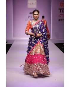 Orange and pink net embroidered lehenga with blue embroidered dupatta 1. Orange and pink net lehenga2. Gota patti work embellished net flare3. Blue floral embroidered lehenga4. Comes with matching unstitched raw silk blouse material and georgette dupatta