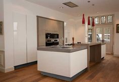 This white kitchen island benefits from a grey worktop and recessed plinth which  together form a 'floating' effect. The kitchen island contains a feature breakfast bar in its centre for a sociable space, as well as a hob, wine cooler, integrated dishwasher, x 2 single sinks, a pull out bin and a towel rail.