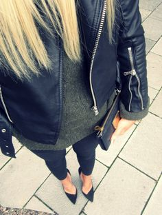 Black leather jacket over a sweater dress with black skinnies and pointy toe pumps