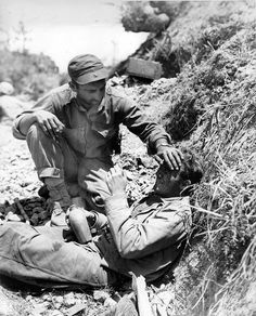 Man of US 1st Marine Division comforting a fellow Marine who had just witnessed the death of a friend Okinawa Japan May 1945.