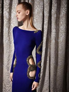 A close up of the side of a long sleeve, cut out and beaded navy blue gown