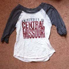 UCM Baseball Tee Preloved University of Central Missouri shirt. The white is burnt out material, and the sleeves are grey with rolled cuffs. Labelled a size medium but fits like a small or extra small. Tops