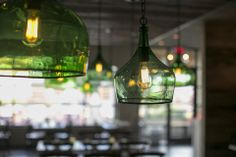 Green hanging glass light fixtures inside Columbia, S.C. Italian restaurant Pasta Fresca. Full-scale commercial interior design project by MACK Home.