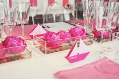 Floating peonies in acrylic containers with clear ghost chairs.