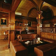 British-inspired home pub/sitting room for relaxing and entertaining. Love the brown woods, artwork, wood detailing, and tufted leather.