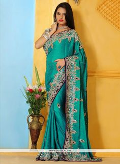 Eyeful teal satin designer saree. Grandeur of the attire is framed by the beads and crystals, resham, stone ornamented foliage patterns. Matching blouse completes the look....