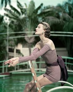 Because sometimes you want your swimsuit to have arms? Model in Striped Bathing Suit by Pool, photographer: John Rawlings 1954