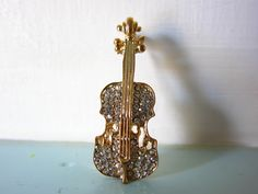 Gold tone Cello brooch / Double bass set with lots of sparkly rhinestones. In good condition with no tarnishing or missing rhinestones. Measures Lightweight so will not drag or pull on clothes. Find more beautiful brooches in my store Gift For Music Lover, Music Lovers, Double Bass, Magpie, Cello, Cottage Chic, Classical Music, Vintage Brooches, Musical Instruments
