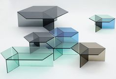 German designer Sebastian Scherer has created a series of tables called Isom. The tables are made completely in 10mm sheets of blue, green, grey, and bronze glass, each with a hexagon-shaped top. Supported by three pieces of rectangular glass vertical panels, the tops appear to form rhombuses when looking down at them because of the edges of the base pieces.