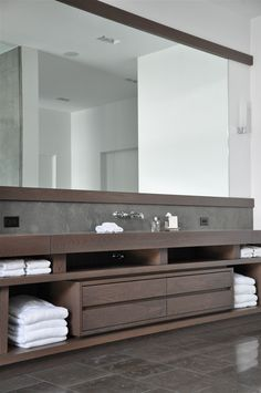 Modern bathroom wood cabinets with a wall to wall mirror.