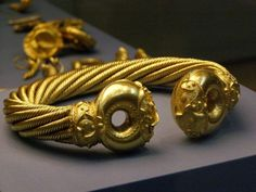 The main part of the torc is made from four ropes, each made from 8 strains of gold wire twisted around each other. The hollow ends are elaborately decorated with La Tène style patterns.