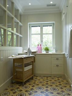small laundry room with beautiful painted floors and a great rolling ironing board/cart
