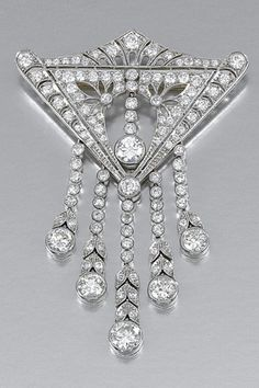 DIAMOND BROOCH, CIRCA 1910 Of stylised pediment design, the central open work motif centring on a pendent line of millegrain-set circular-cut diamonds, suspending a similarly-set tassel embellished with foliate links