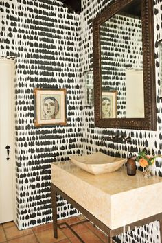 Schumacher's Queen of Spain wallpaper defines a powder room, where a custom console fabricated by Gearhart Ironwerks is topped with a custom slab from Alpha StoneWorks in Portland. The sconces are from The Urban Electric Co., and a custom mirror is from Lara Sydney Framing Gallery, also in Portland.