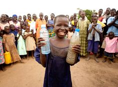 Rebecca smiles in rural Uganda, holding bottles of the dirty water she used to drink and the clean water her village now uses.