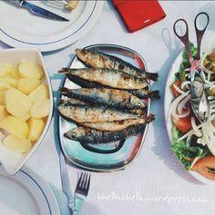 Sunbathing while eating sardinhes grelhado (grilled sardines).